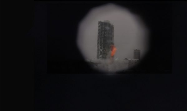 Through a peephole, a burning building fallen down